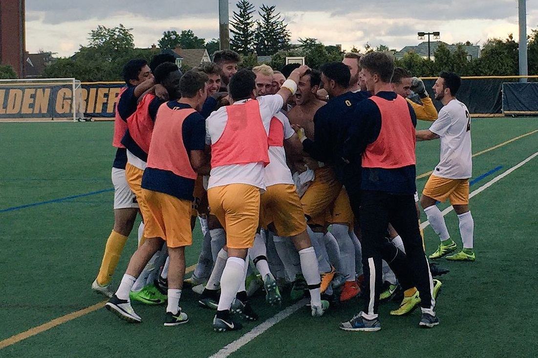 Canisius men's soccer team mobs Troy Brady, who scored the game-winning goal in overtime. (Ben Tsujimoto/Buffalo News)