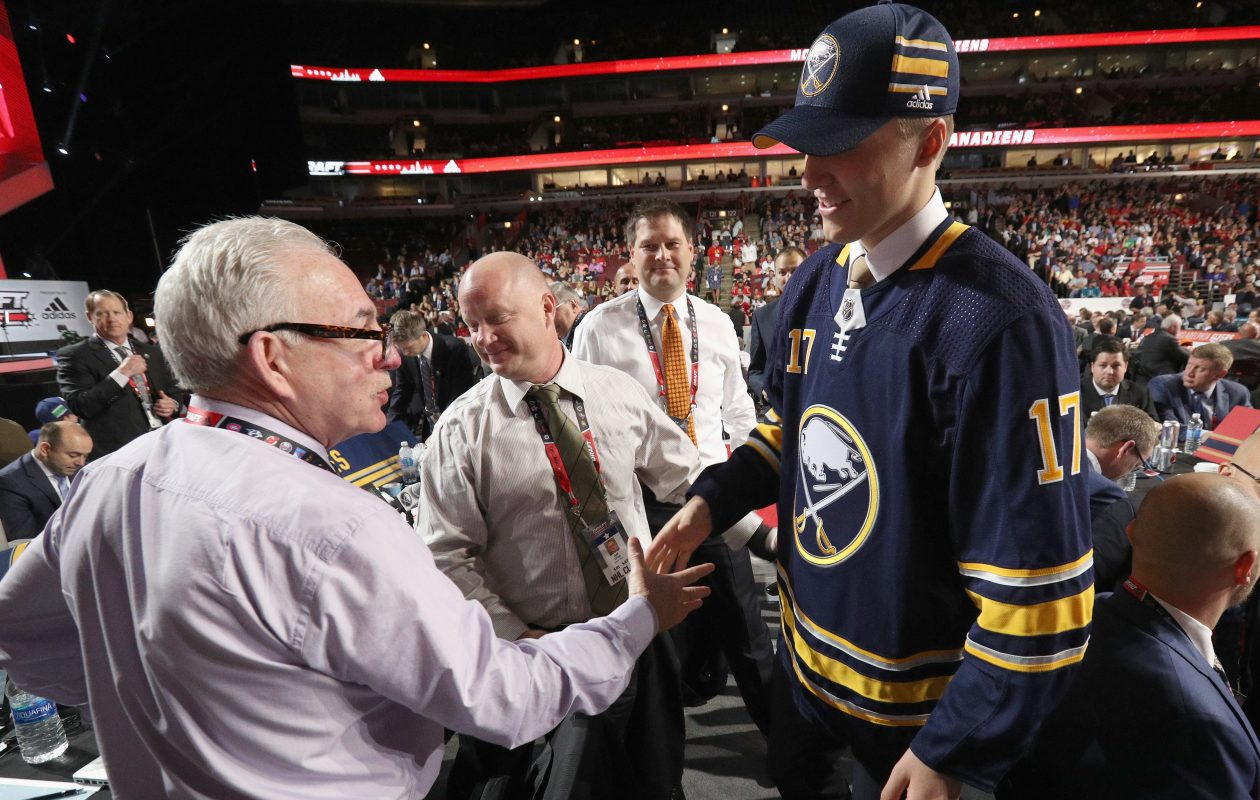 Kevin Devine, who has been reassigned as an amateur scout, shakes hands with second-round draft pick Ukko-Pekka Luukkonen in June as Jeff Crisp and Jason Botterill wait their turns. (NHLI via Getty Images)