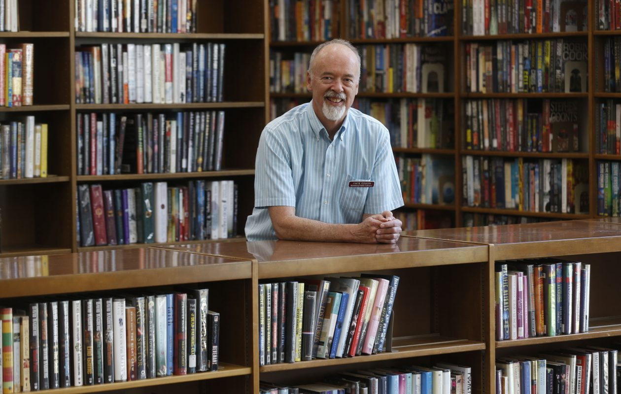 Hamburg Public Library Director Jack Edson, who is retiring at the end of this month, stands near a stack of books at the library at 102 S. Buffalo St. in Hamburg on Thursday, Aug. 3, 2017.  (Robert Kirkham/Buffalo News)