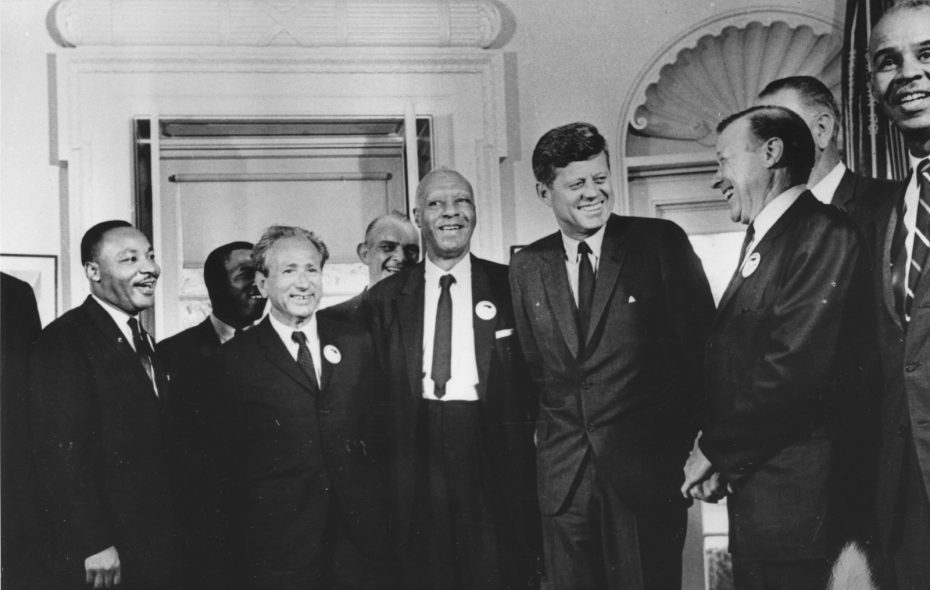 President John F. Kennedy in the White House with leaders of the civil rights 'March on Washington' (left to right) Whitney Young, Dr Martin Luther King (1929  - 1968), Rabbi Joachim Prinz, A. Philip Randolph, President Kennedy, Walter Reuther (1907 - 1970) and Roy Wilkins. Behind Reuther is Vice-President Lyndon Johnson. (Three Lions/Getty Images)