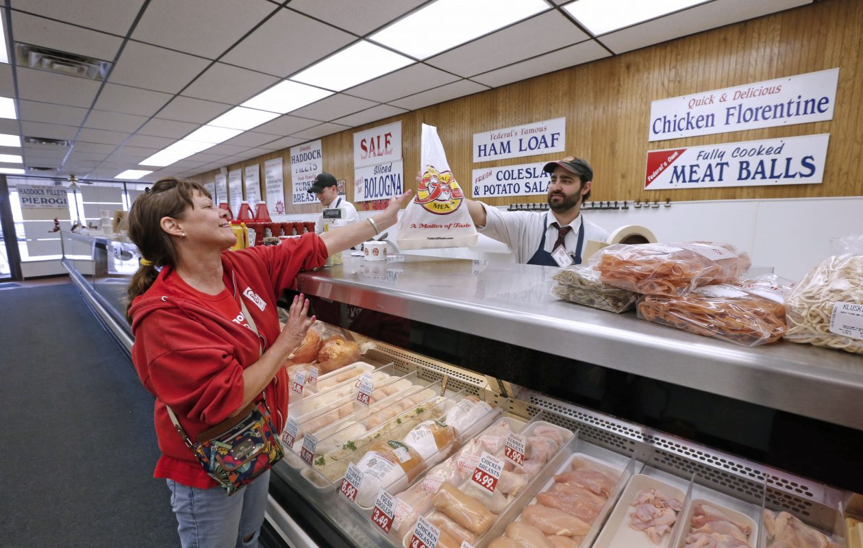 Customer Sandy Mick, left, picks up her order at a Federal Meats store in Northtown Plaza from assistant manager Ryan Vara in this April 19, 2017 file photo. The Federal Meats store closed Aug. 5, 2017, becoming the latest store to leave the plaza. (Robert Kirkham/Buffalo News)