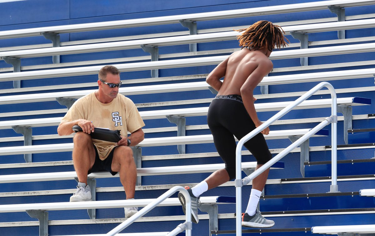 Rich Lowe, left, times one of his players during a drill Monday. Lowe enters his 20th season with the Sweet Home football program but his first as head coach. (Harry Scull Jr./Buffalo News)