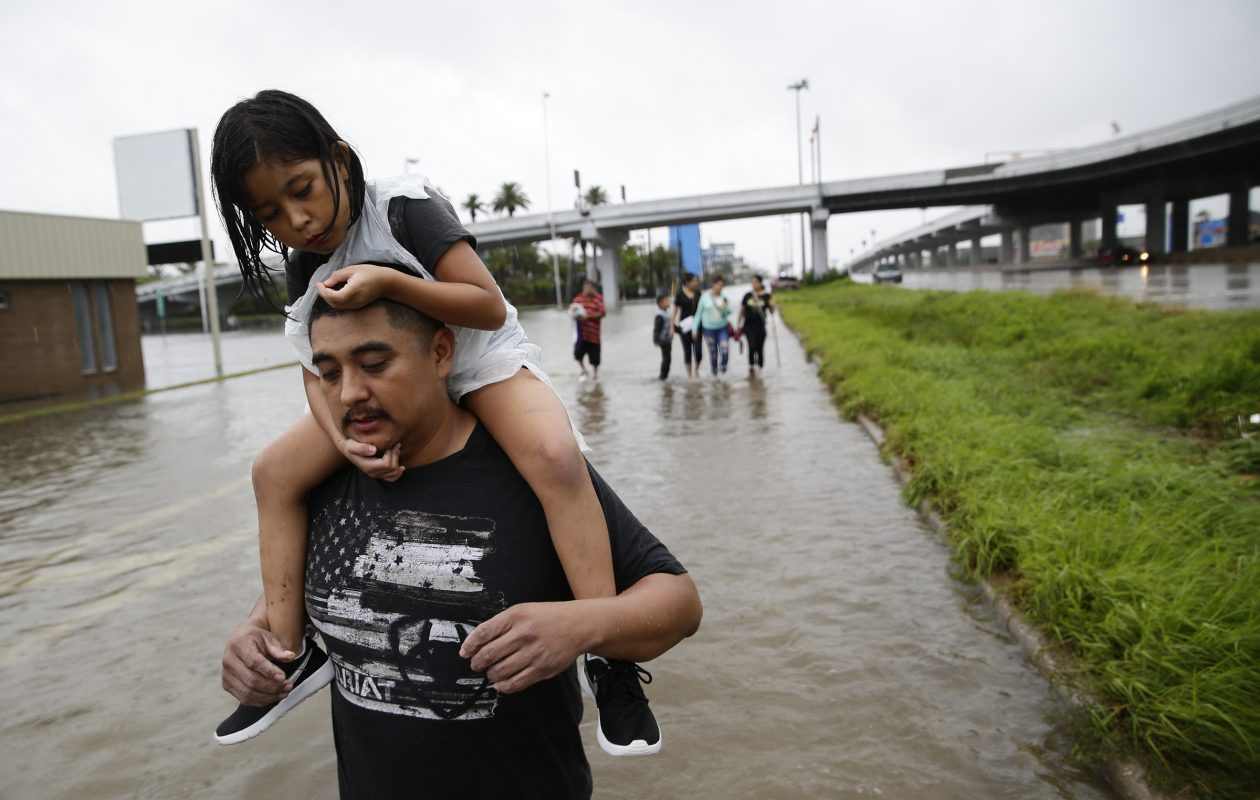 Jesus Nunez carries his daughter Genesis, 6, as he and numerous family members flee their flooded home, walking nearly four hours to the safety of a relative's house on Sunday, Aug. 27, 2017, as Tropical Storm Harvey continues to cause major flooding throughout Southeast Texas. (Robert Gauthier/Los Angeles Times/TNS)