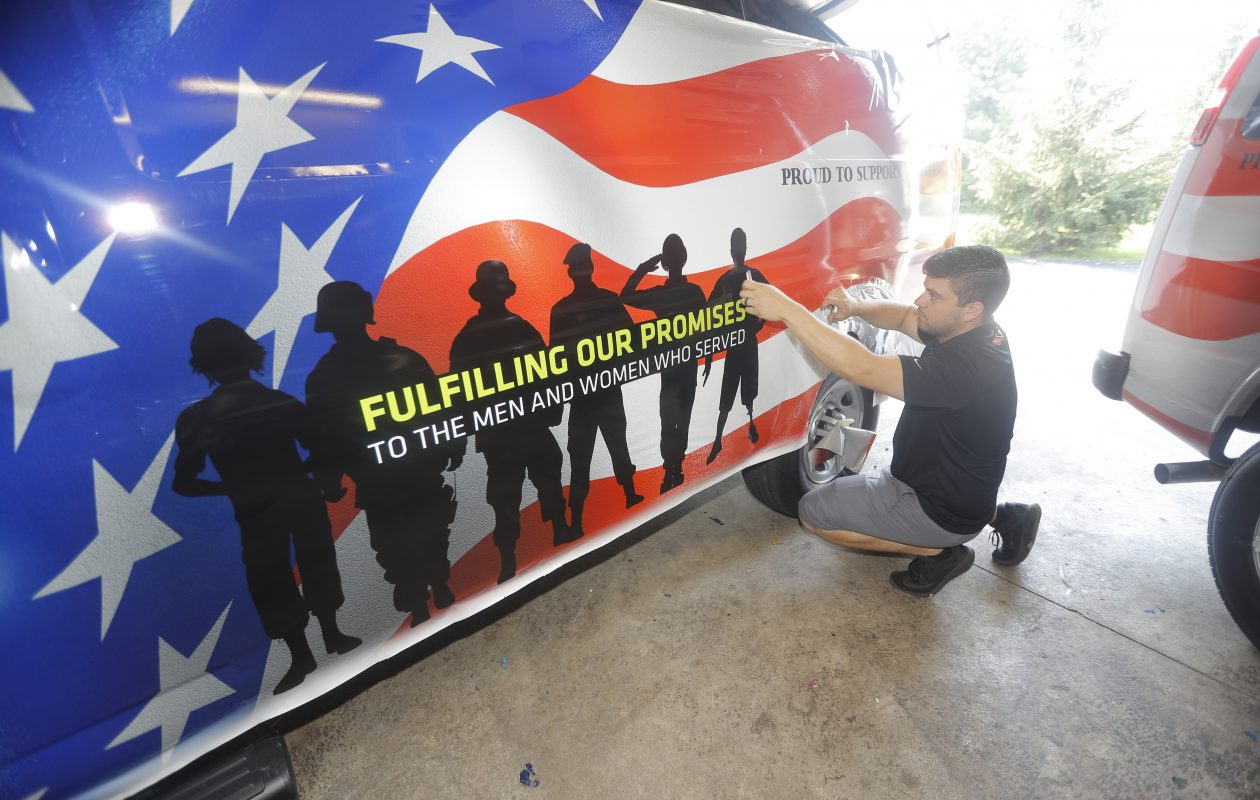 Tyler Lorich of Streamline Designs, in North Tonawanda, applies  patriotic vinyl graphics to one of 10 vans that restaurateur Russell Salvatore is donating to transport veterans to and from the Buffalo VA Medical Center. Lorich was photographed Thursday, Aug. 3, 2017.   (John Hickey/Buffalo News)