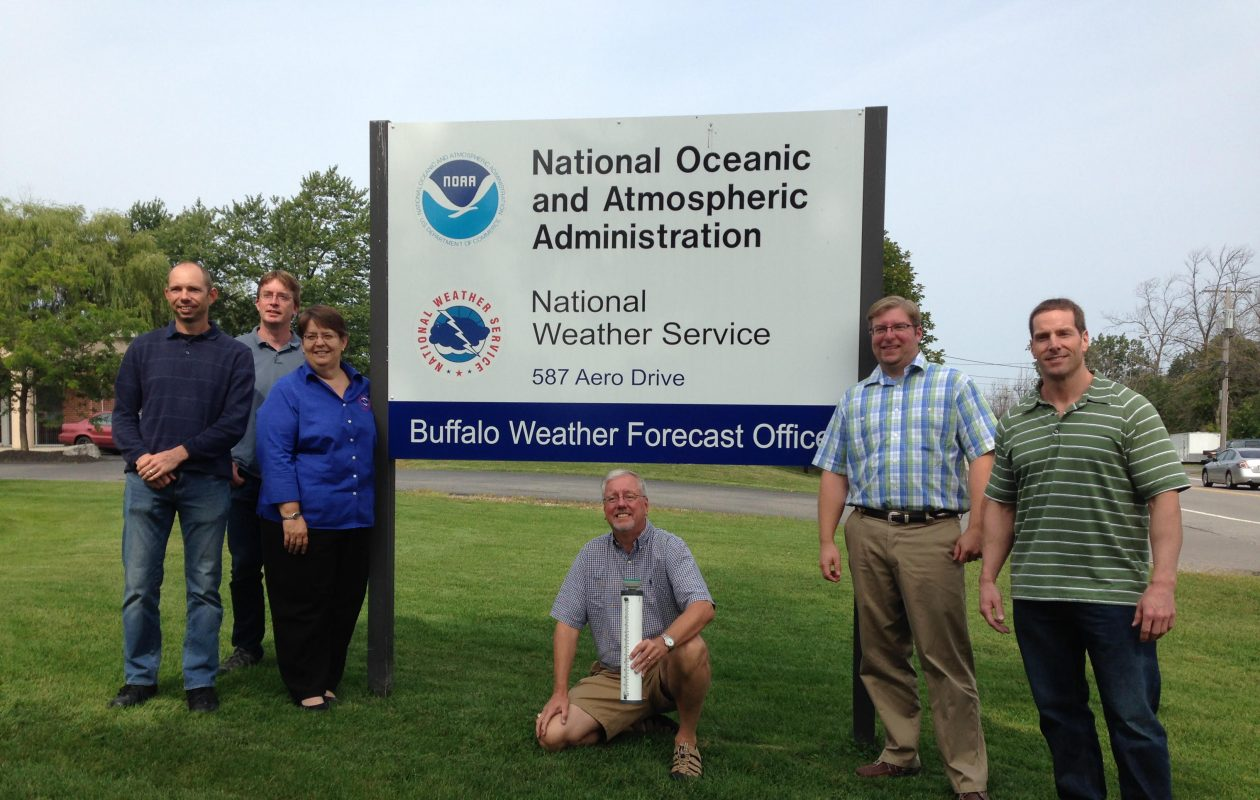 Kneeling under the sign outside the National Weather Service in Buffalo Monday is Henry W. Reges, a Colorado State University meteorologist and the national coordinator of the CoCoRaHS network. He met with forecasters at the weather service including (from left to right) meteorologists Kirk Apffel, Dan Kelly, Judy Levan, Jon Hitchcock and Jim Mitchell)