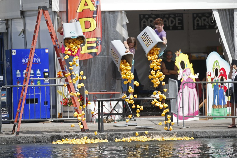 From left, Hank Sokol, Gabe Sharpless and Charlotte Morvile launch hundreds of rubber ducks near the Blue Line Bridge at Canalside during the Buffalo Rotary's Duck Derby fundraiser Sunday. (Robert Kirkham/Buffalo News)