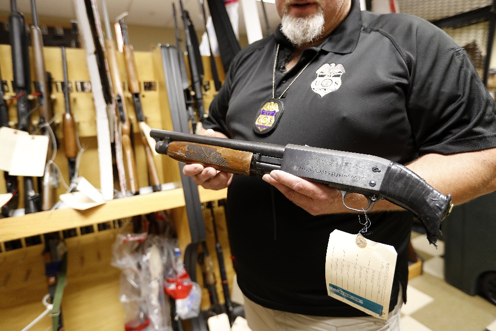 Local ATF agent in charge Steve Dickey holds one of the guns authorities seized as other confiscated  guns line the wall  in the agency's storage locker. (Mark Mulville/Buffalo News)
