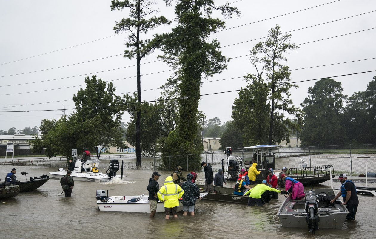 Volunteers in boats rescue people and their pets from their homes near Interstate 45 in Houston.  (Washington Post photo by Jabin Botsford)