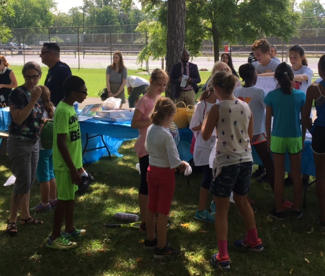 Youngsters from PAL's Tennis Camp get their 'Love to Serve' shirts that honor Natalie Lewis.