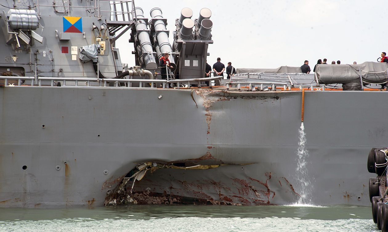 Damage to the portside is visible as the guided-missile destroyer USS John S. McCain steers towards Changi Naval Base in Singapore, following a collision with a merchant vessel. (U.S. Navy photo by Mass Communication Specialist 2nd Class Joshua Fulton)