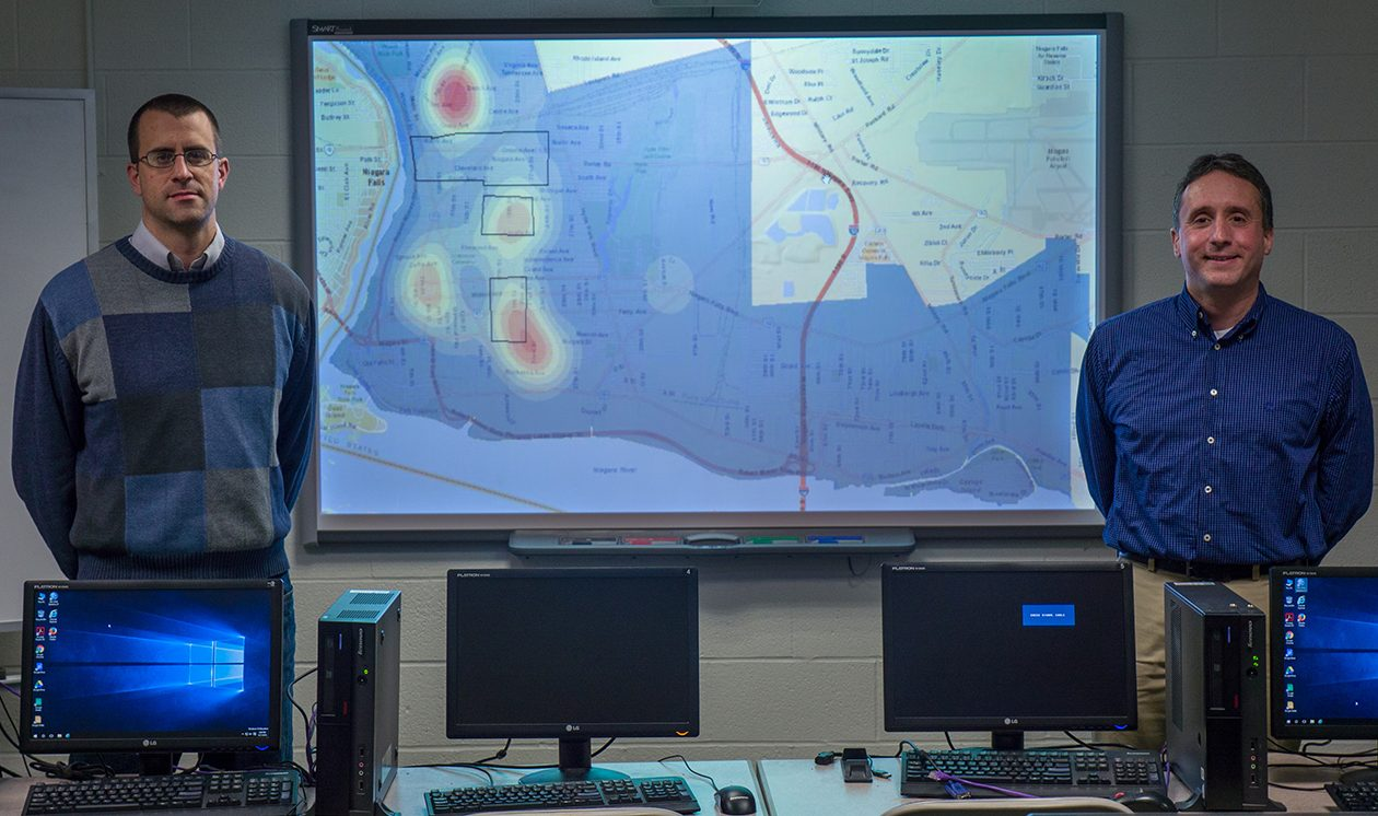 Niagara University criminal justice professors Timothy Lauger (left) and Craig Rivera (right) pose with their computerized map of crime hotspots in Niagara Falls. (Courtesy Niagara University)