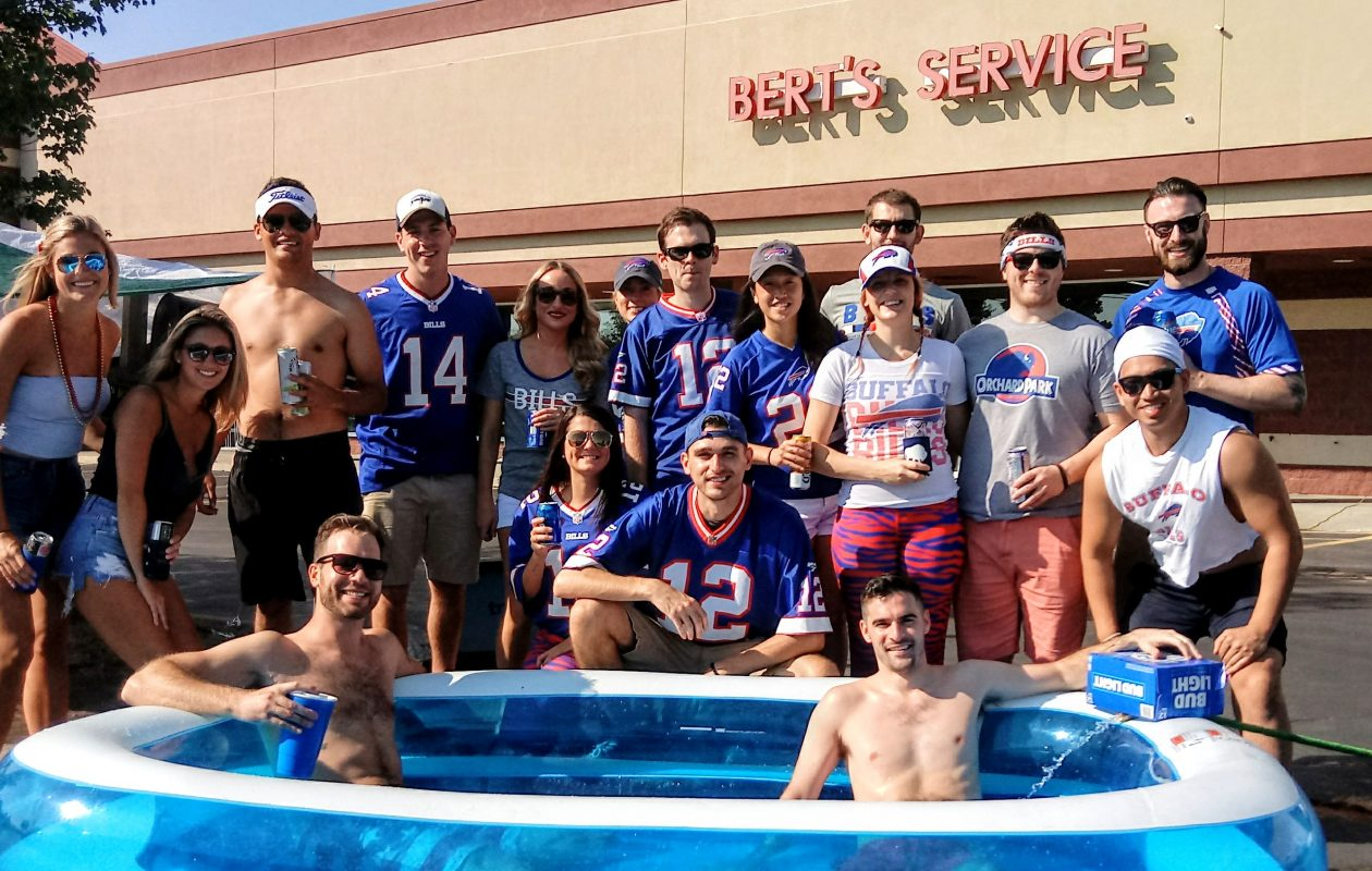 David Pels (left) and Jeff Willis, both of Buffalo, lounge in an inflatable pool surrounded by a group of friends outside Bert's Bikes & Fitness before the Bills game Sunday, Sept. 24, 2017. (Luke Hammill/Special to The News)