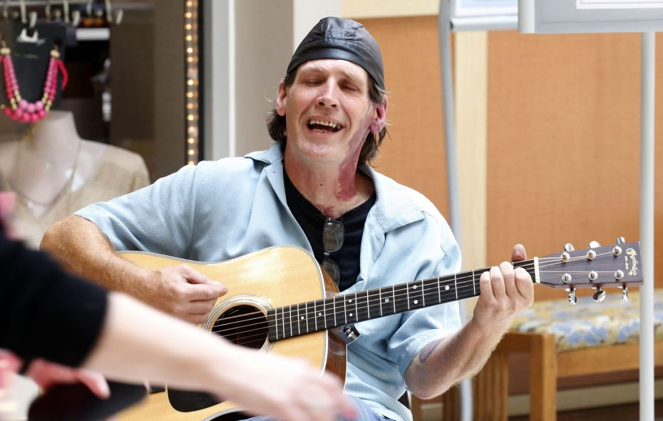 Michael Casinelli sings and plays his guitar in the Roswell Park lobby.  (Robert Kirkham/Buffalo News)