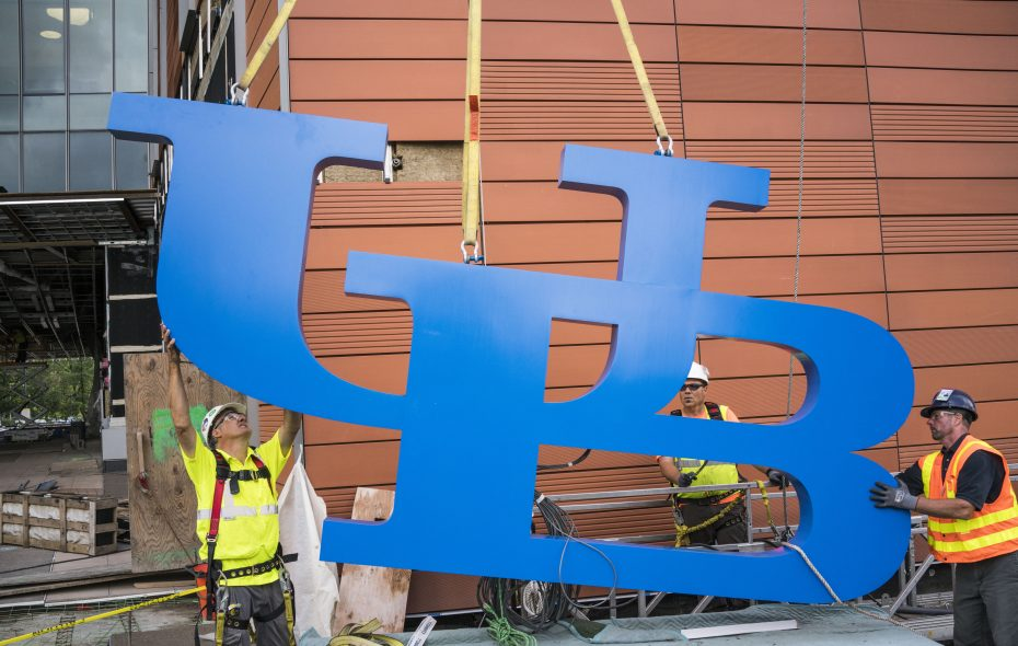 Workers guide a giant, 800-pound UB logo as it is lifted by crane towards its new position atop the new UB Jacobs School of Medicine and Biomedical Sciences on the Buffalo Niagara Medical Campus in August.  (Derek Gee/Buffalo News file photo)