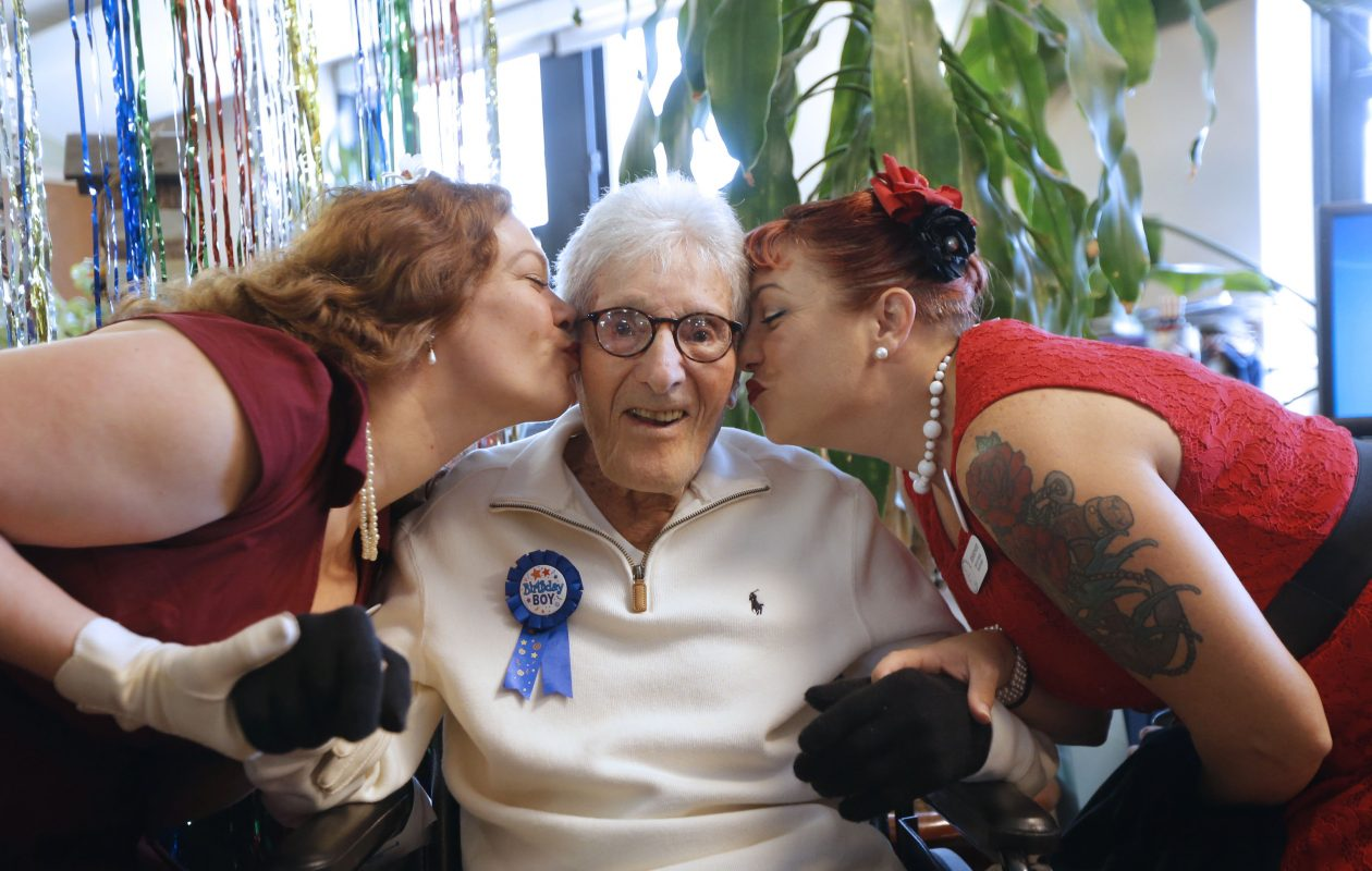 Veteran Sydney Cole celebrated his 103rd birthday at the Buffalo VA. Friday. WWII -era period actresses from 'Pin-ups for a Cause' service organization Miss Mouse Kittear, left, and Kimmy-Sue, right, treated him to a birthday kiss at his party.    (Robert Kirkham/Buffalo News)