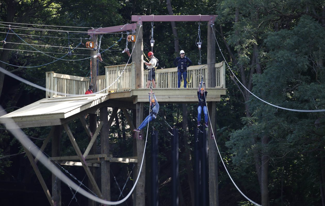 The Niagara Zipper is a new zip line attraction adjacent to the Lockport Caves. It crosses the Erie Canal and back. Kirsten Ritchie, left, and her sister, Kateyln, of Lockport, make the second run of the ride. (Sharon Cantillon/Buffalo News)