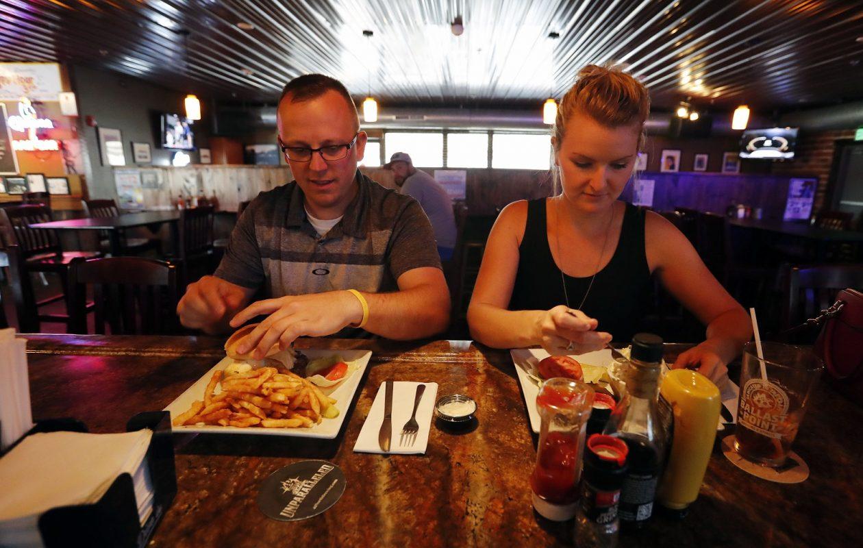 Jason Sobczynski enjoys a Buck Wild burger and Ashley Hoch enjoys a bacon cheeseburger at Buffalo's Best Grill in Orchard Park. (Mark Mulville/Buffalo News)