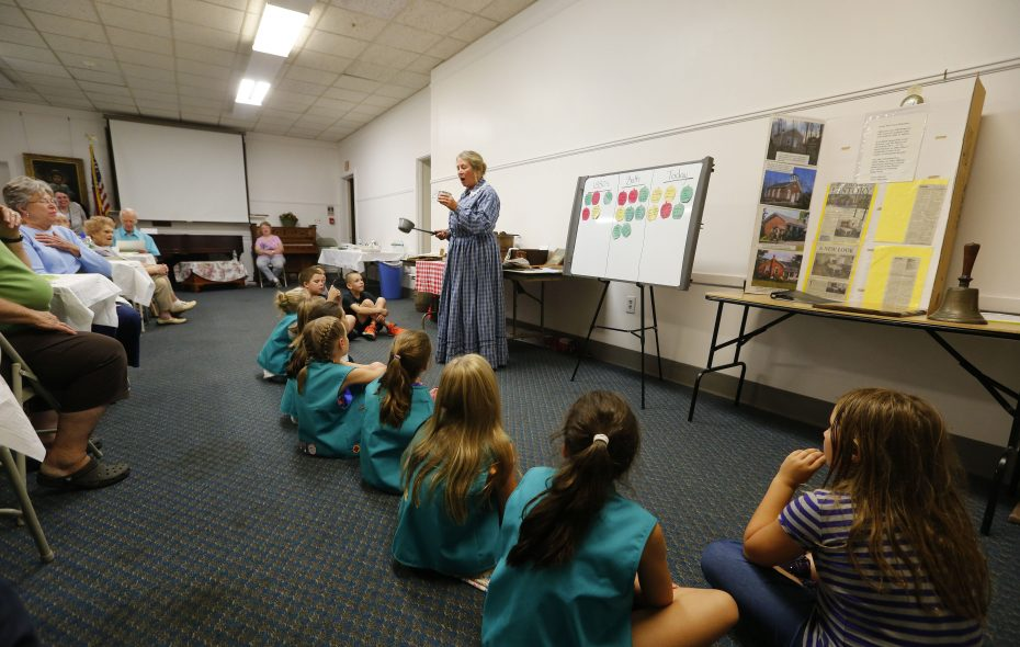 Adults and youngsters alike were attentive as Karen Sherwood portrayed a late 19th century schoolteacher during Family Night in the Niagara History Center in Lockport. She divided the young pupils into groups of boys and girls, as would have been done in a one-room schoolhouse. (Mark Mulville/Buffalo News)