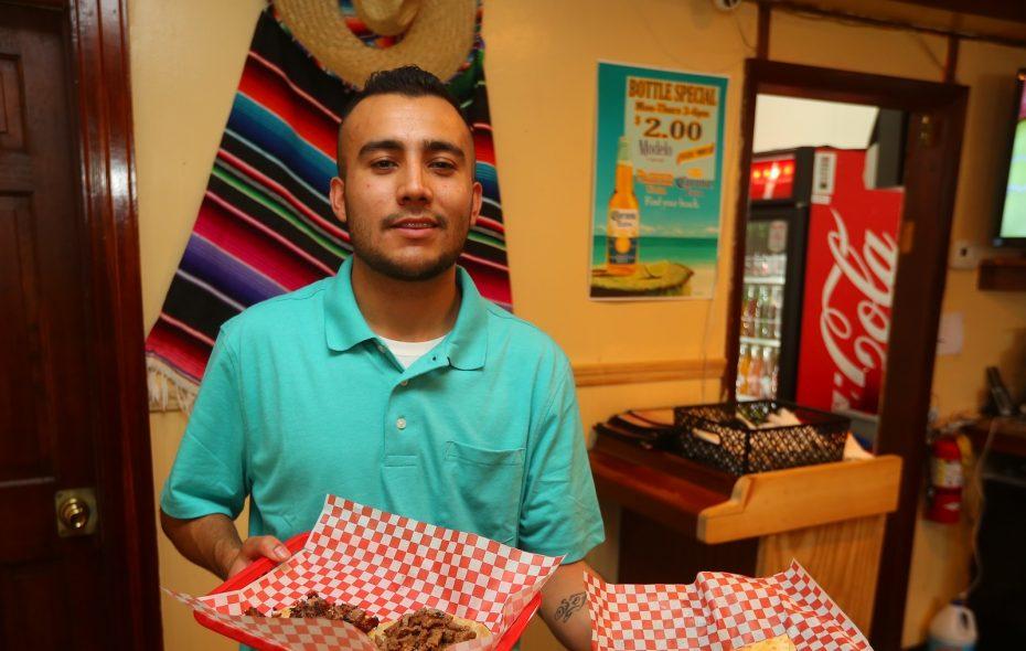 Taqueria los Mayas server Jaime Castro brings out food. (John Hickey/Buffalo News)