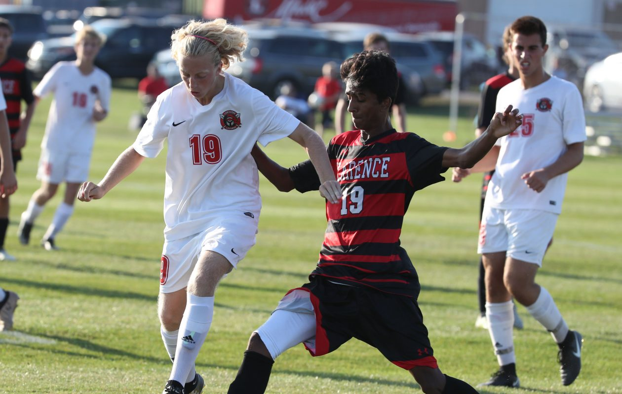 Clarence's Taha Ahmed battles Lancaster's Tyler Eisman for the ball in front of the net during the Red Devils' win. (James P. McCoy/Buffalo News)