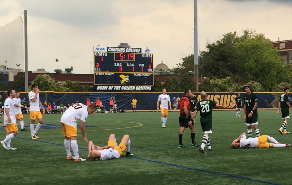 Canisius players Filippo Tamburini, on the ground left, and Hunter Walsh writhe on the ground after two Scott Williams fouls. (Ben Tsujimoto/Buffalo News)