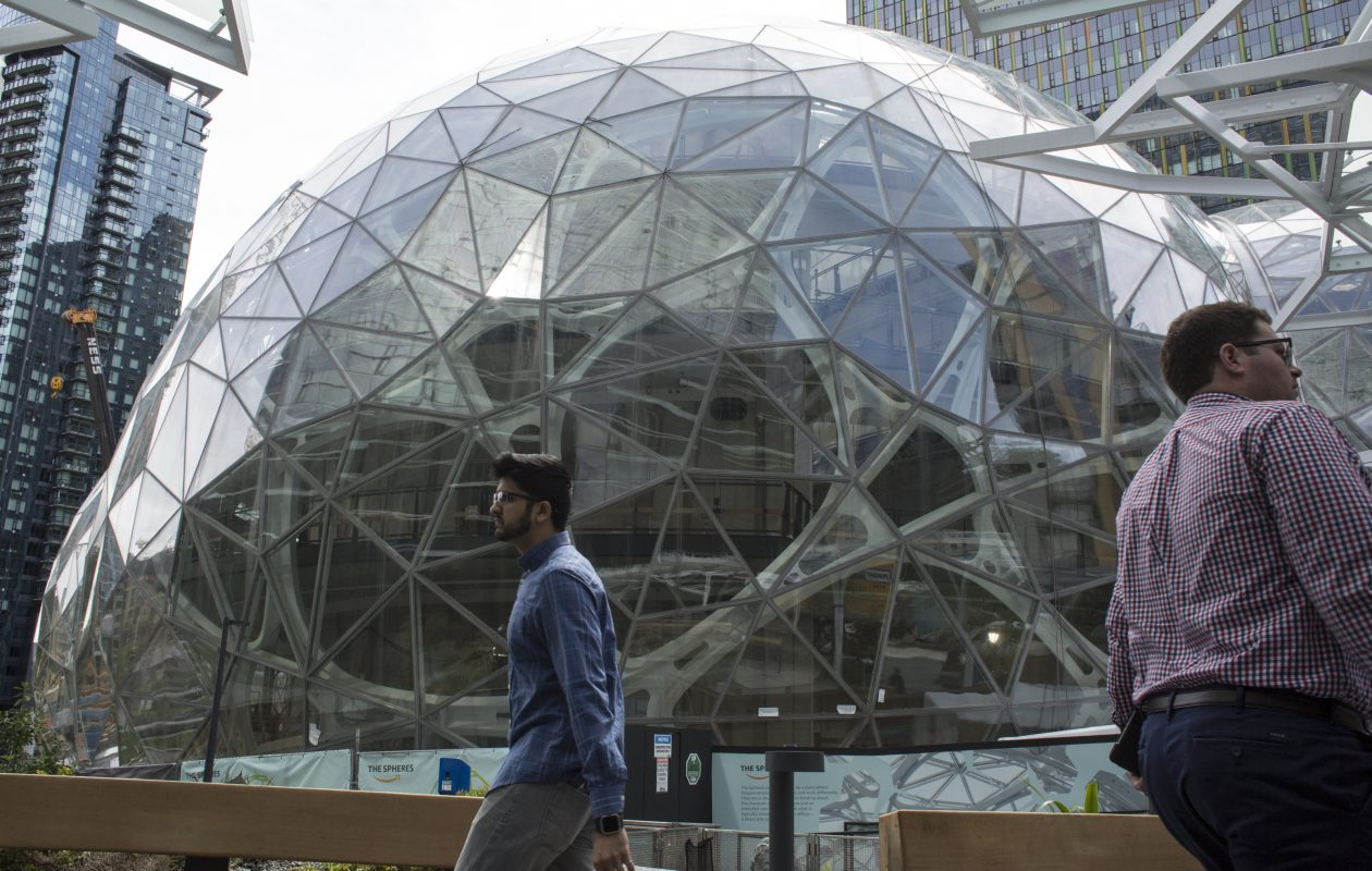 People walk past the signature glass spheres under construction at the Amazon corporate headquarters on June 16, 2017, in Seattle. (Photo by David Ryder/Getty Images)
