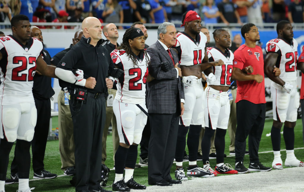 Atlanta Falcons owner Arthur Blank joins arms with his players during the playing of the national anthem prior to Sunday's game against the Detroit Lions at Ford Field in Detroit. (Getty Images)