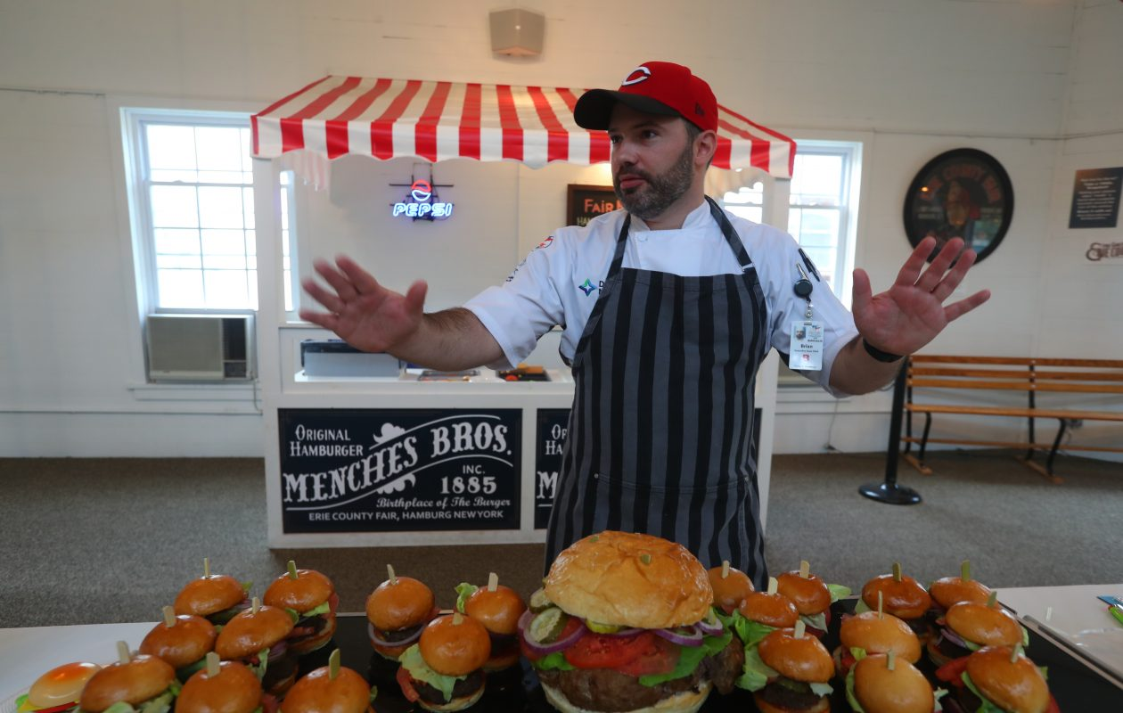 Brian Waters, executive chef at Delaware North Companies, presents an oversized hamburger cooked for a National Birth of the Burger Day   ceremony by the culinary staff of Hamburg Gaming on Monday, September 18th, 2017 at the Hamburg Fairgrounds.  Hamburg, N.Y. is believed to be where the hamburger was invented, at the 1885 Erie County Fair by Frank and Charles Menches. (John Hickey/Buffalo News)