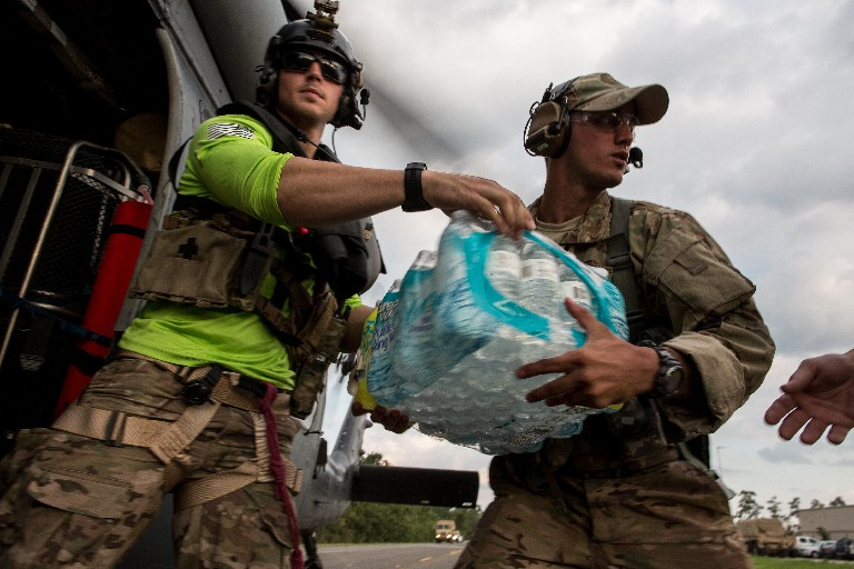 Members of a pararescue team deliver cases of bottled water at a staging area in Beaumont, Texas, Friday. (New York Times)