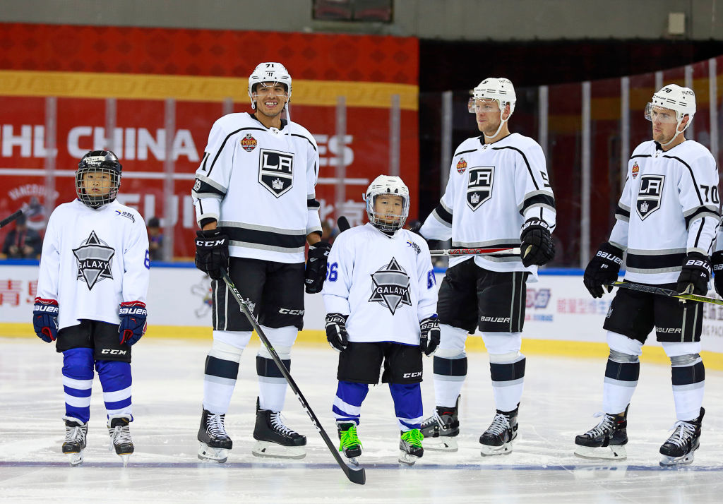 Jordan Nolan, left, with teammates Christian Folin and Tanner Pearson, stands with Chinese children for the national anthem prior to Saturday's preseason game against Vancouver in Beijing (Photo by Jeff Vinnick/NHLI via Getty Images).