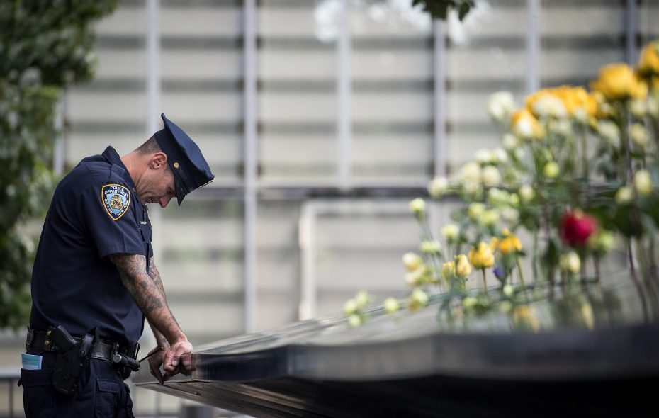 A New York City police officer pauses while visiting the North pool during a commemoration ceremony Monday for the victims of the Sept. 11 terrorist attacks at the National September 11 Memorial in New York City. (Drew Angerer/Getty Images)