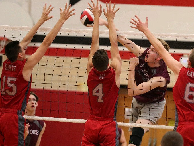 St. Joe's Connor Wolbert spikes the ball past Lancaster's Brandon Smith (15) and Alan Au (4) in the first set at Lancaster, which won in three sets. (James P. McCoy/Buffalo News)