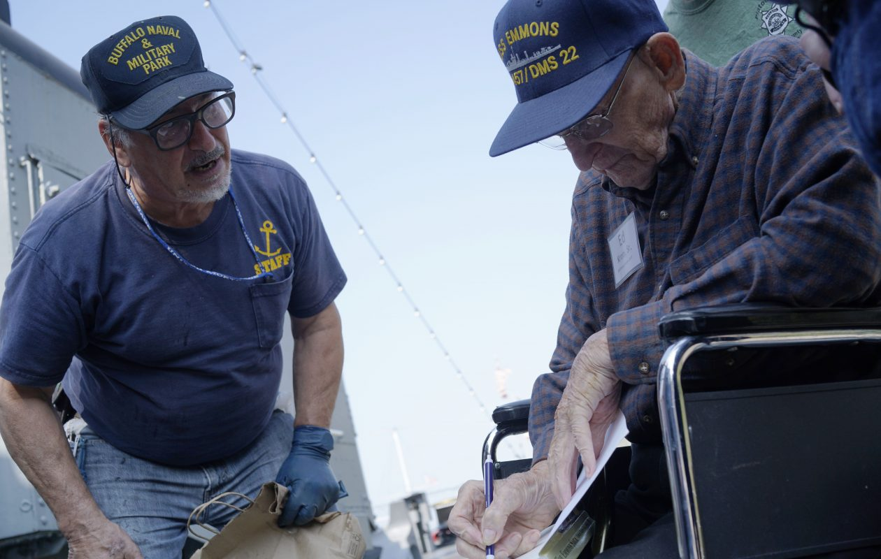 WWII veterans and USS Emmons survivor Ed Krom Sr., right, signs a copy of a book for naval park staff Jim Marzullo as Krom tours the USS The Sullivans during the USS Emmons 2017 Reunion at the Buffalo and Erie County Naval and Military Park, Friday, Sept. 15, 2017.  (Derek Gee/Buffalo News)