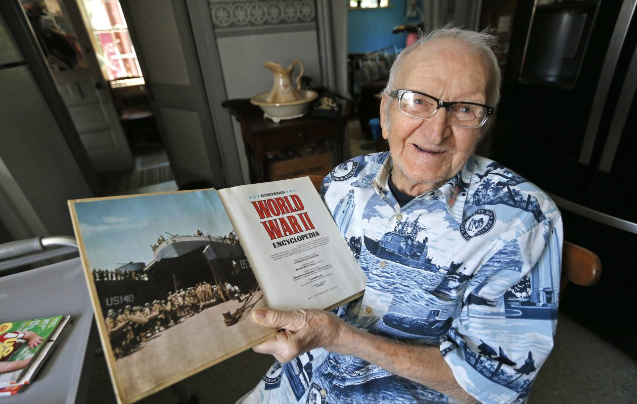WWII Navy veteran Stanley T. Witczak holds a military encylopedia that displays a photo of him on his ship.   (Robert Kirkham/Buffalo News)