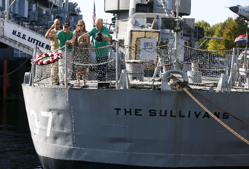 From left to right: Mark Pijacki, Rich Cuttone, Kelly Sullivan, and John Mataka, throw a wreath off the fantail of the USS The Sullivans on Friday during a reunion at the Buffalo and Erie County Naval and Military Park for those who served on the ship. (Mark Mulville/Buffalo News)