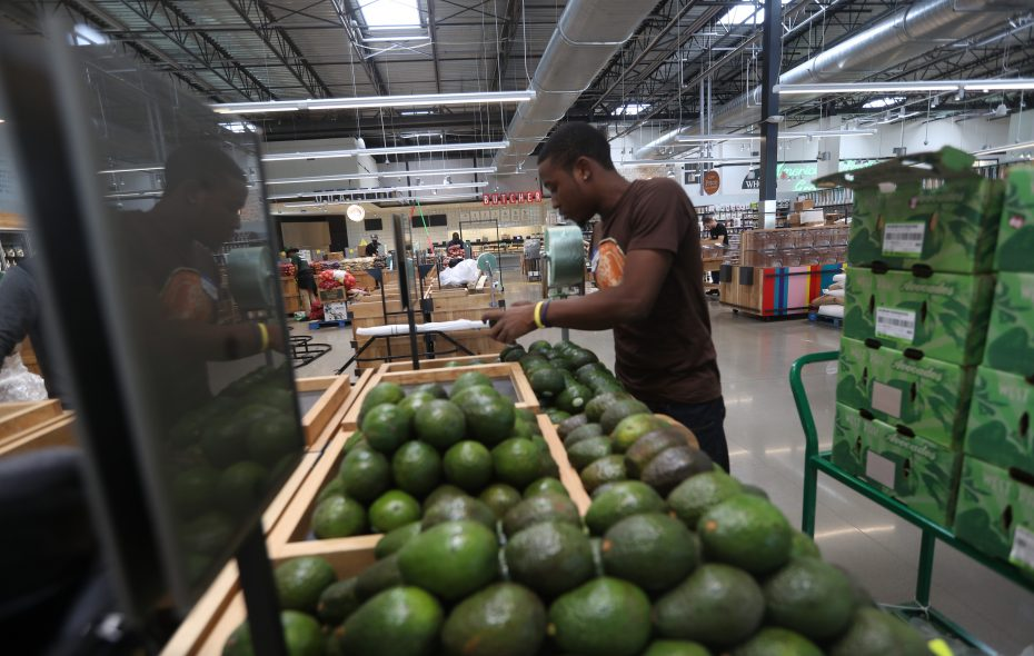 Marcial Michelle, a produce supervisor, stocks avocados on Tuesday, Sept. 12, 2017 while preparing for the Sept. 15 opening of Whole Foods Market. (John Hickey/Buffalo News)