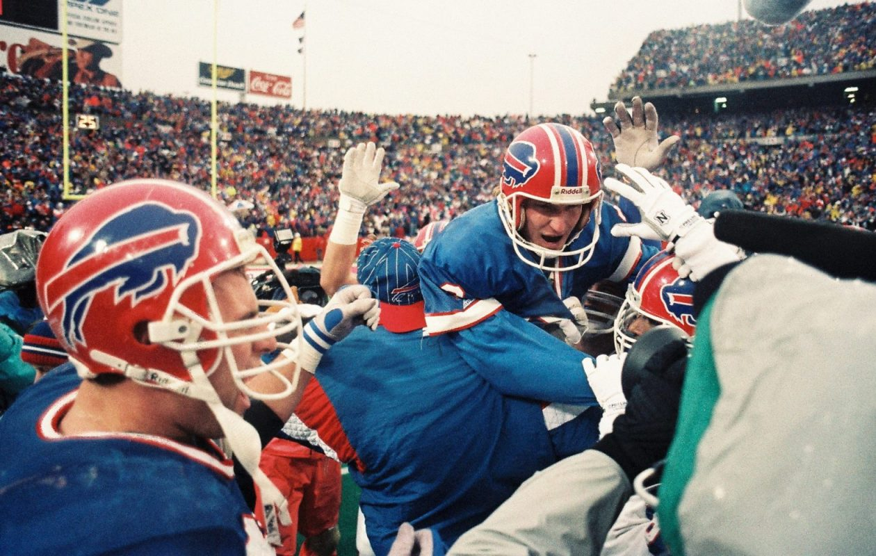 Steve Christie is mobbed by his Bills teammates shortly after the game-winning kick against the Oilers. (James P. McCoy/Buffalo News)
