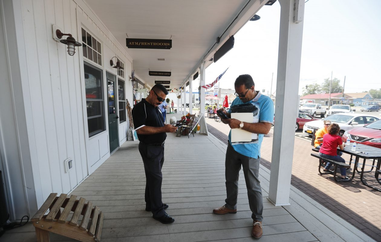 Mayor Willie Rosas of Dunkirk (left) and his brother Hector Jr. check their phones in July on the city's boardwalk: Thus far, no luck in reaching their mother after a hurricane. (Mark Mulville/The Buffalo News)