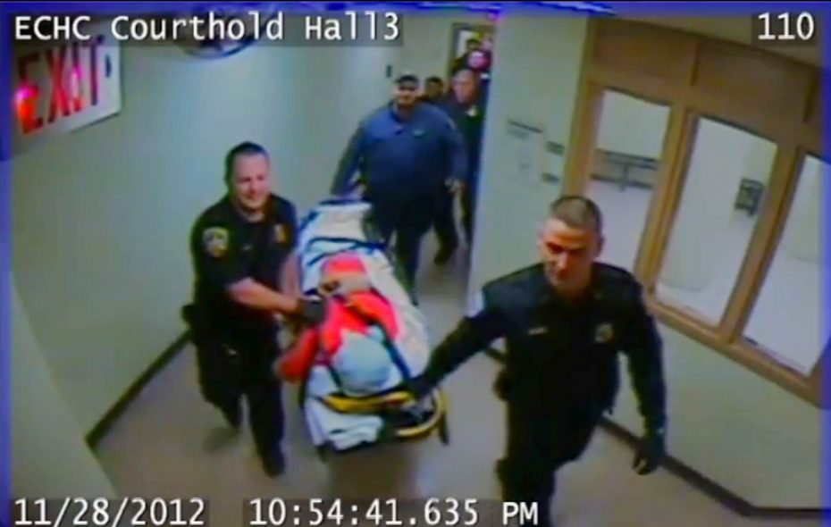 Still frame from surveillance video shows Richard A. Metcalf Jr., with a spit mask tied tightly around his neck and a pillow case covering his head, being wheeled out of the Holding Center. He died later at ECMC.