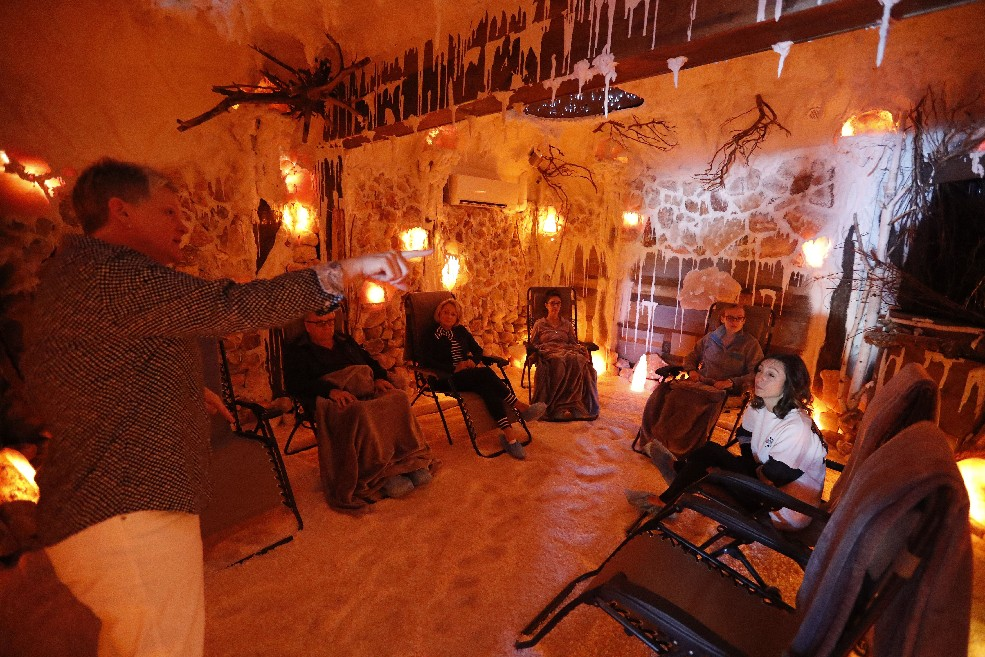 Co-owner Tadgi DeBerg speaks with customers before their session in the salt cave at  AURA salt cave and wellness in Clarence. (Mark Mulville/Buffalo News)