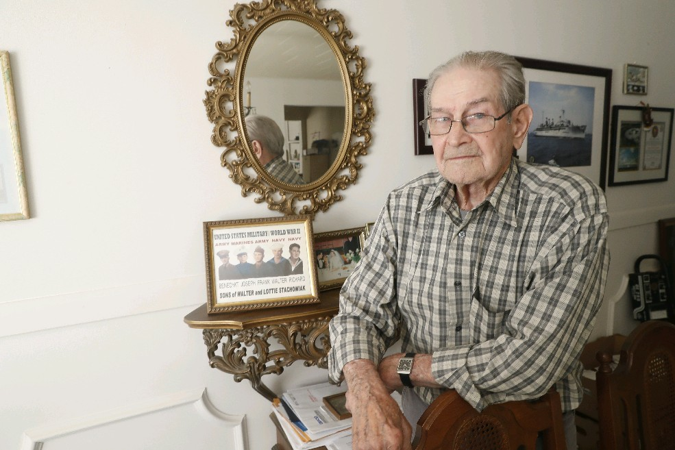 Richard J. Stachowiak, known as an 'atomic veteran' because of his exposure to atomic bomb tests at the Bikini Atoll, was one of five brothers who served in World War II. The five are depicted in the photo behind him. (John Hickey/Buffalo News)
