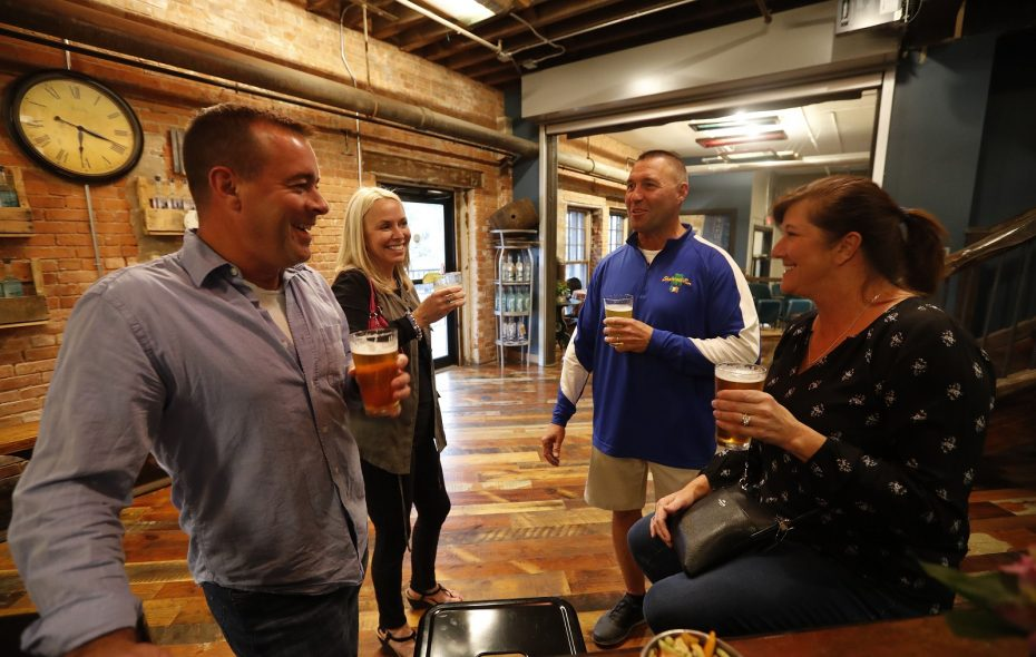 """Pressure Drop Brewing Company, in The Barrel Factory, will participate Thursday in the Hammer & Ales fundraiser to benefit Habitat for Humanity Buffalo. From left, Adam and Roni Howell and Mike and Kim Burlow enjoy a pint in  Lakeward Distillery, which also serves Pressure Drop craft beer and is in The Barrel Factory . """"If you come for nothing else, you've got to see this place. It's stunning inside,"""" Stephanie Lawson, development and communications manager for the Buffalo Habitat chapter, said of the fundraising venue, which sits in a restored building in the Old First Ward. (Mark Mulville/Buffalo News)"""