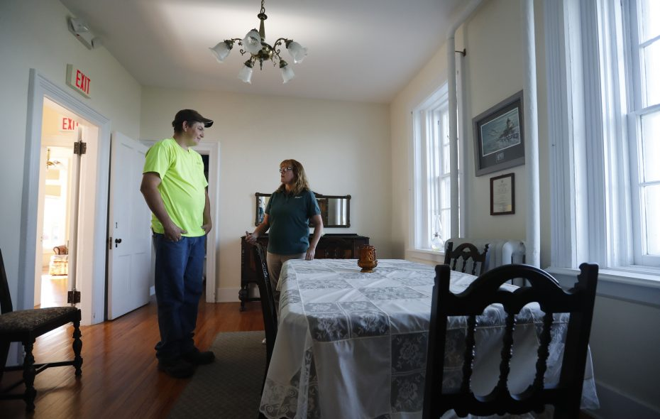 Brandon Sandolfini talks with Barbara Larson in the dining area of the Thirty Mile Point Lighthouse in Golden Hill State Park.  Both Sandolfini and Larson, who work at the park, have had eerie experiences in the lighthouse building. (Mark Mulville/Buffalo News)
