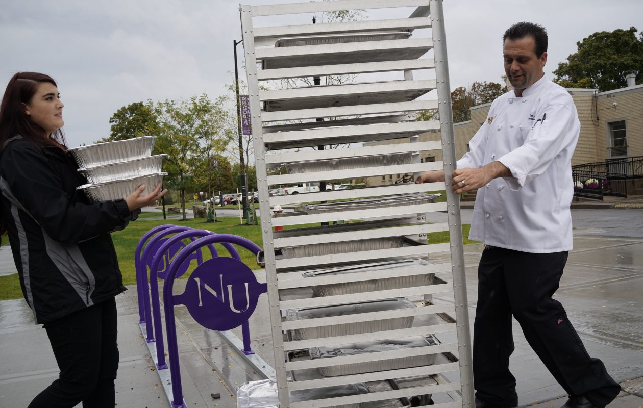 Nicole Slipko, catering sales manager, and Tony Renda, executive chef for Metz Culinary Management, which runs the dining operations at Niagara University, carry trays of unused food that are being donated to the Community Missions in Niagara Falls.  (Derek Gee/Buffalo News)