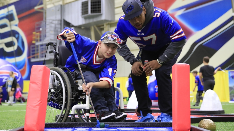 Buffalo Bills Lorenzo Alexander helps Ian Cameron, 13, from Grand island line up a putt during a family fun night with games and activities for children with pediatric cancer at the ADPRO Sports Training Center at One Bills Drive on Tuesday, Oct. 17, 2017. (Harry Scull Jr./Buffalo News)
