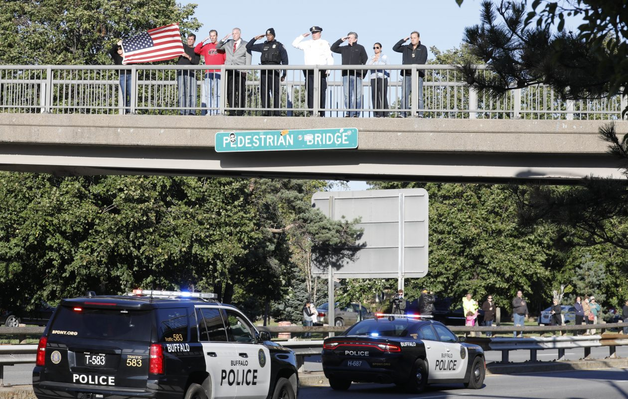 Buffalo police officers salute from the pedestrian bridge over the 198 as the procession escorting the body of Buffalo Police Officer Craig Lehner passes en route to Erie County Medical Center, Tuesday, Oct. 17, 2017.  (Derek Gee/Buffalo News)