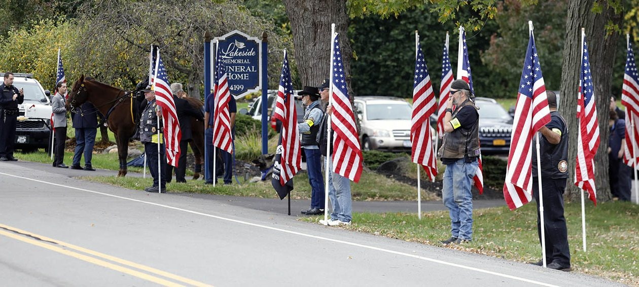 Patriot Guard Riders with flags line Camp Road outside the Lakeside Memorial Funeral Home in Hamburg to pay tribute to fallen BPD Officer Craig Lehner on Oct. 23. The funeral procession for Lehner will travel along Route 5 in Hamburg into Buffalo. (Derek Gee/Buffalo News)