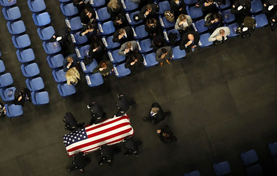 Mourners salute as pallbearers pass by carrying the casket of Buffalo police Officer Craig Lehner out of KeyBank Center in Buffalo on Wednesday,. (Mark Mulville/Buffalo News)
