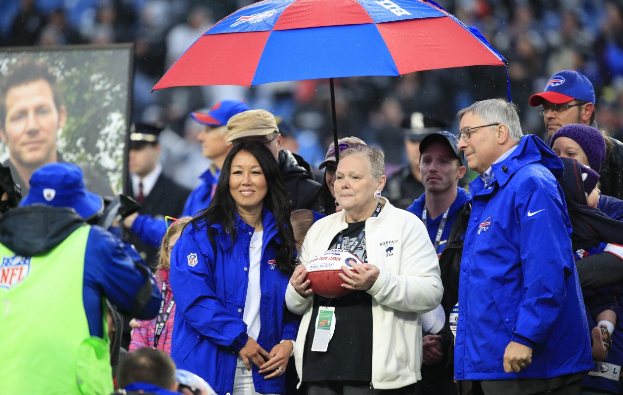 Buffalo Bills owners Kim and Terry Pegula present a game ball to the family of fallen BPD Officer Craig Lehner. (Harry Scull Jr./Buffalo News)