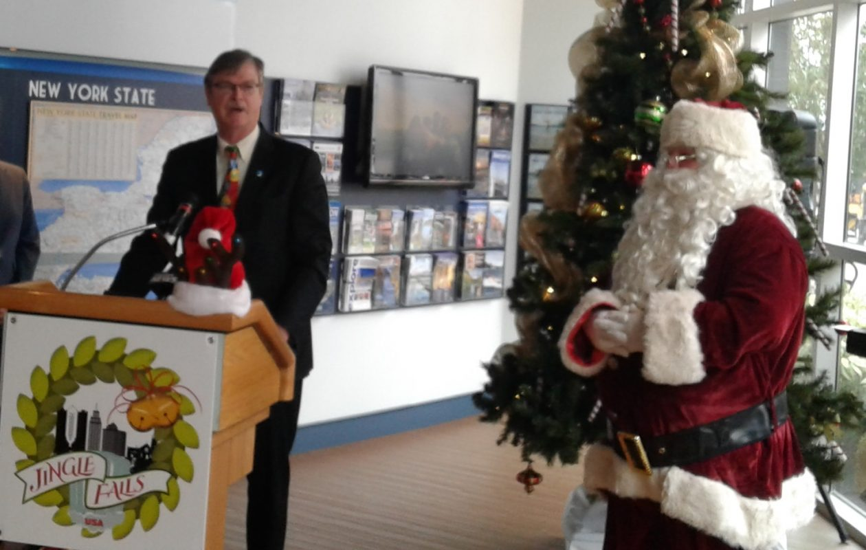 Santa Claus looks on as Niagara Falls Mayor Paul A. Dyster speaks at a news conference for the city's Jingle Falls USA holiday promotion Oct. 12, 2017, in the city visitor center. (Thomas J. Prohaska/The Buffalo News)